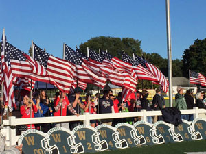 Students-from-CHS-and-WSH-hold-flags-to-honor-our-community's-veterans,-active-service-members,-and-first-responders